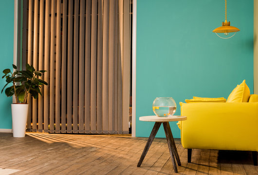 yellow sofa and aquarium with fish on table in living room