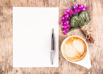 Cup of morning coffee, letter and flowers. Romantic concept. Cup of cappuccino on wooden background.