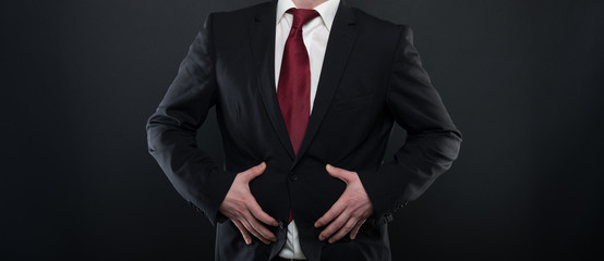 Business man wearing black suit holding belly like hurting.