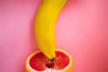 banana with red grapefruit on pink background, sex concept