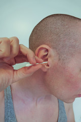 A guy cleans the ears from ear wax with a cotton swab.