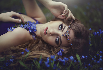 Elf girl with long hair and blue eyes in the tiara rests in spring forest blue forest flowers. Girl Princess dreams. Wall mural