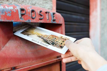 Male hand is drops a postcard in a red postbox in Venice, Italy. The postcard shows a Venice canal.