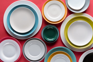 White and colorful plates of different sizes on red background