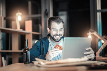 Pizza time. Delighted positive IT guy eating pizza while looking down and smiling