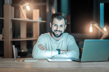 Perfect job. Gay bearded IT guy posing at table while smiling and looking at camera