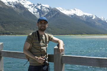 Hombre joven con gorra frente a paisaje de picos de montañas nevados y verdes con cielo azul frente a un lago en Nueva Zelanda
