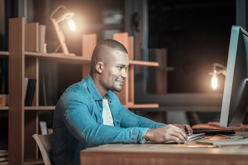 Art of programming. Optimistic handsome IT guy working on computer while posing in profile and smiling