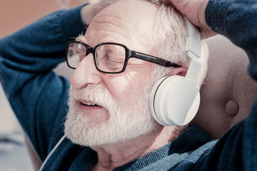 Pleasant relaxation. Portrait of a positive relaxed aged man wearing headphones while listening to music