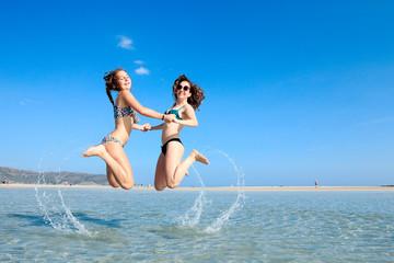 jeunes filles heureuse sautant  dans l'eau