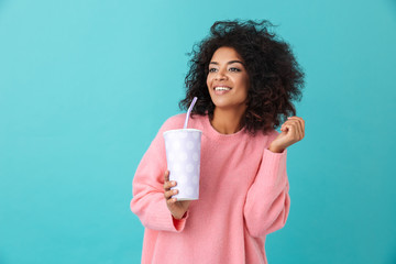 Portrait of adorable woman 20s with afro hairdo looking aside while holding soda beverage in paper cup, isolated over blue background