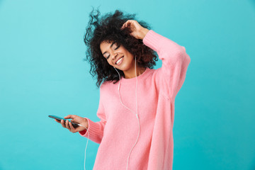 Joyous american woman in casual clothing dancing and listening to music with pleasure via white earphones, isolated over blue background