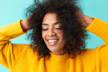 Lovely curly woman in basic clothing llaughing and grabbing her head, isolated over blue background