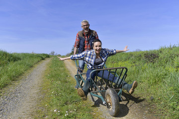 Farmer pushing woman in wheelbarrow