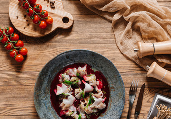 top view of delicious Ceviche with dorado and fresh tomatoes on wooden table