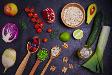 Selection of healthy food. Food background: quinoa, pomegranate, lime, green peas, berries, avocado, nuts and olive oil. Slate banner background. overhead, horizontal