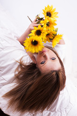 Beautiful young woman with sunflower lying in bed