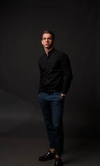 attractive white man in black shirt and blue pants stands on a dark background