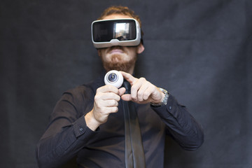 Elegant hipster with virtual reality goggles, posing on black background