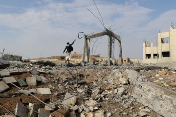 Man is seen at the site of an airstrike that destroyed the Community College in Saada