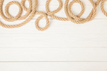 top view of brown nautical rope on white wooden background
