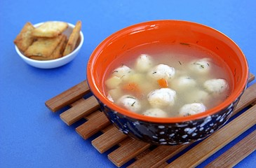 Light vegetable soup with semolina dumplings on a blue background