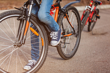Child on a bicycle at asphalt road in sunny spring day. Closeup on pedal and foot