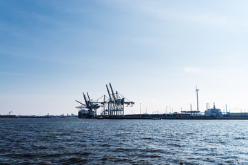 Hamburg harbor with cranes at commercial dock under blue sky