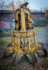 Huge old claw on the ground detached from excavator