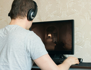 Man in headphones playing computer shooter game.