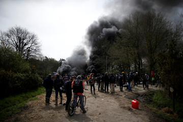 Protesters gather near burning debris that barricades a road as French gendarmes continue an evacuation operation in the zoned ZAD (Deferred Development Zone) at Notre-Dame-des-Landes