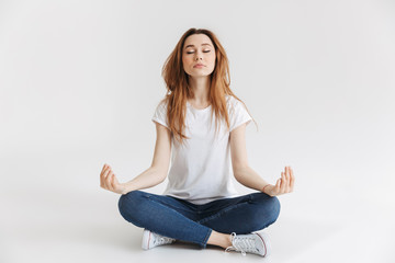 Calm woman in t-shirt sitting on the floor and meditation
