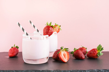 Strawberry milkshake with berry on pink. Close up. Summer drink.