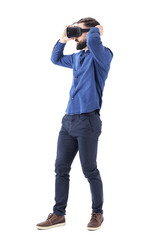Side view of serious young bearded business man putting on virtual reality glasses. Full body length isolated on white background.
