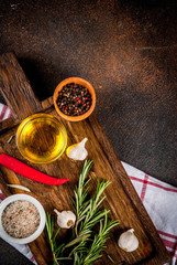 Cooking background, herbs, salt, spices, olive oil on cutting board, dark rusty background copy space top view