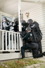 Police tactical team gathered round a house