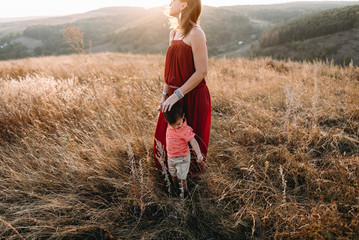 beautiful young mother in a long red dress easy walks with her young son. Summer, sunset, high yellow grass, mountains. He is on the hands, holding the hand