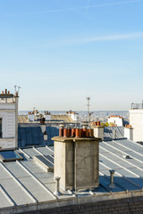 Papiers peints Art Studio Open view over the rooftops of Montmartre district in Paris with zinc roofing, TV antennas, skylights and a group of chimneys in the foreground under a clear blue sky.