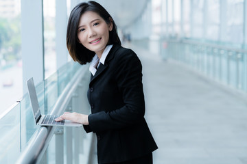 smart beautiful asian woman with laptop business concept with blur corridor background