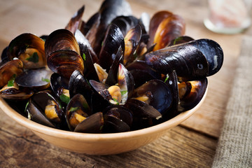 Black mussels on plate with green on wooden board