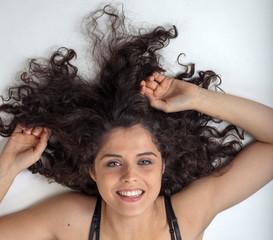 Donna con capelli sparsi a terra sorride