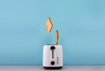 Roasted toast bread popping up of stainless steel toaster on a blue backgroun. Wall mural