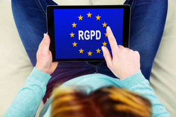 Woman using a touch pad with Flag of European Union with RGPD word inside on the screen