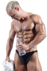 Handsome muscular man relaxing after hard training in front of white background