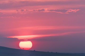 Beautiful rural landscape with a big setting sun, Dobrogea, Romania