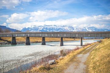 alte Holzbrücke führt über einen Fluss inmitten von Bergen