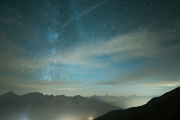 Milky Way galaxy and starry sky from high elevation in summertime on the Alps. Fog and mist, city lights.