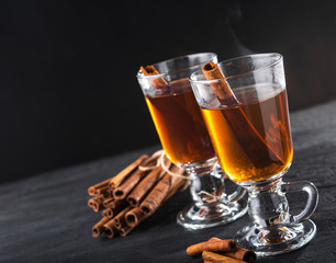 Freshly brewed black tea with cinnamon, in transparent cups on a dark background.Copy space