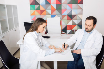 Two doctors sitting in the clinic office and sign documents