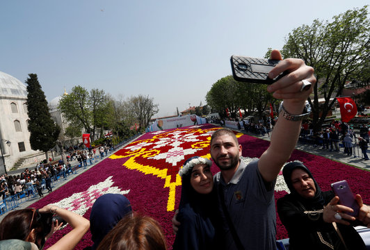 People pose for selfie with a huge carpet design formed by tulips at Sultanahmet square during the 13th Tulip Festival in Istanbul
